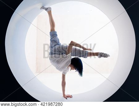 Flexible Girl Doing Stretching And Handstand In Studio. Concept Of Healthy Lifestyle And Yoga
