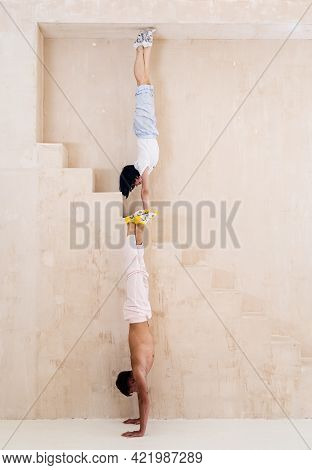 Flexible Girl And Man Doing Stretching And Handstand In Studio. Concept Of Individuality, Creativity