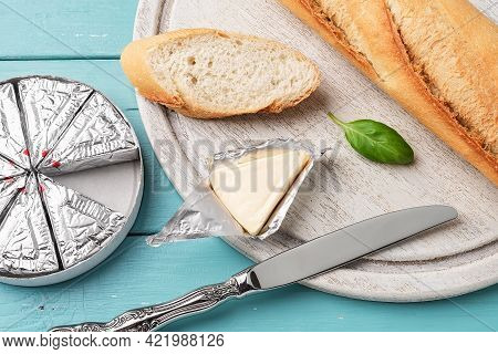 Foil Wrapped Processed Cream Cheese, Table Knife And Slice Of Bread On A Cutting Board Over Blue Woo