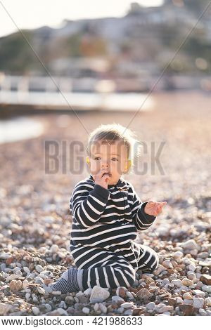 Little Boy In Striped Overalls Sits On His Knees On A Pebble Beach With A Pebble In His Mouth
