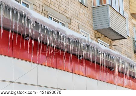 Long, Even Icicles Hang From The Roof Against The Backdrop Of The House. The Wall Of The Building Is