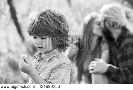 Pledge Of Love. Little Child With Couple Kissing On Background. Small Child Hold Spring Flower. Cute