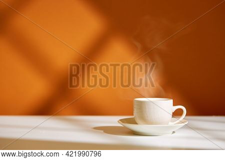 Close-up of coffee cup on table at direct sunlight. Morning coffee with steam in white cup.