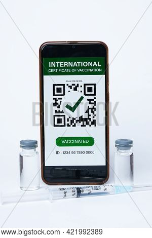 A Picture Of Smartphone With International Certificate Of Vaccination On It, Two Doses Of Vaccine An