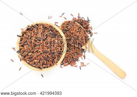 Top View Of Dry Organic Brown And Riceberry Rice Seeds In Wooden Bowl And Spoon On White Background,