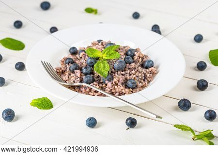 Delicious Risotto With Blueberries Served On White Wooden Table