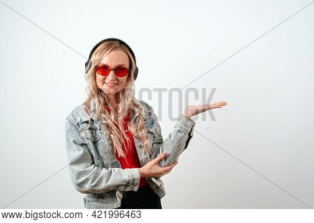 Portrait Of A Blonde Woman In Headphones On A White Background, Hold A Hand, Advertising, Promo Poin