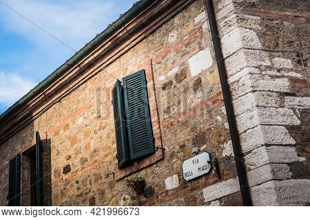 San Quirico D'orcia, Tuscany, Italy - August 18 2020: Traditional Tuscan Stone House With Green Wood