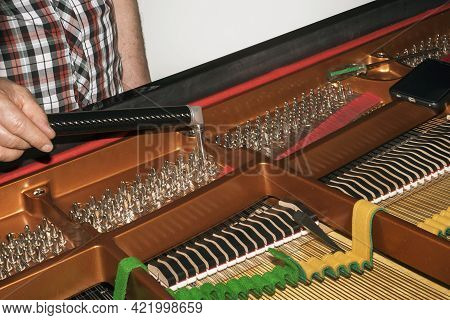 Closeup Of A Piano Tuner Hand With Ratchet At Wotk