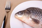 Fresh fish carp on white plate and fork closeup poster