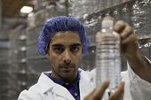 Portrait of factory worker holding water bottle poster