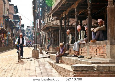 BHAKTAPUR - MAY 20 : Unidentified Tharu old men besides the street of Bhaktapur, Nepal on May 20, 2013. Tharu are an ethnic group from west part of Nepal.
