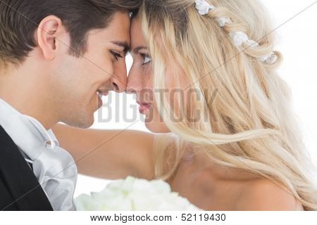 Happy young married couple looking each other in the face on white background