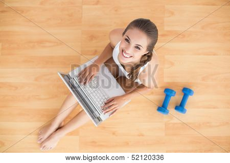 Smiling sporty brunette using a laptop and sitting next to dumbbells on the floor