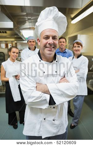 Head chef posing with his team behind him in restaurant kitchen