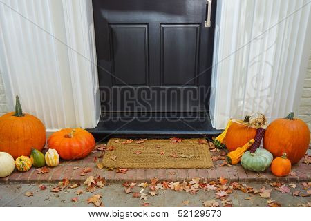 Pumpkins on front steps of home during  Halloween/Thanksgiving season poster