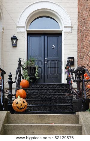 Halloween decorated front door with various size and shape pumpkins