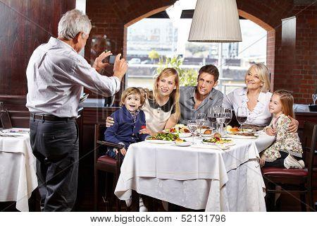 Opa macht ein Familienfoto beim Restaurantbesuch mit dem Smartphone