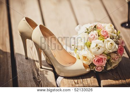 Close up of wedding bouquet and bride shoes poster