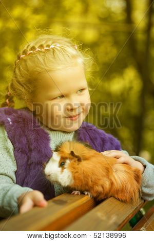 Slyly smiling girl posing with guinea pig