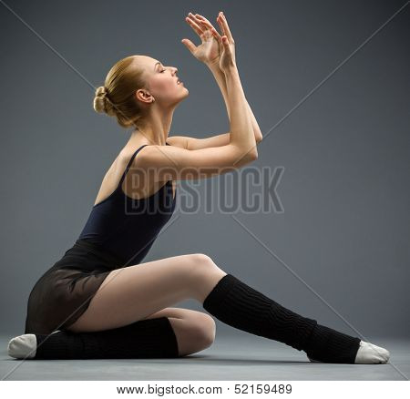Dancing on the floor ballerina with hands up, isolated on grey. Concept of elegant art and sportive hobby