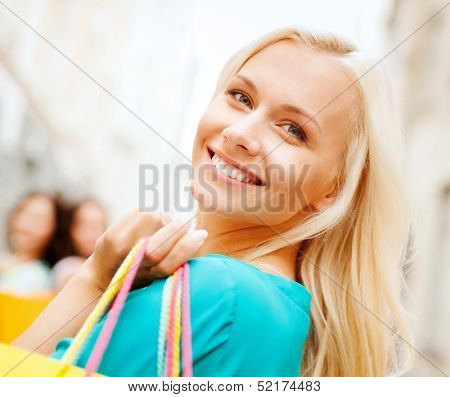 shopping and tourism concept - beautiful woman with shopping bags in ctiy