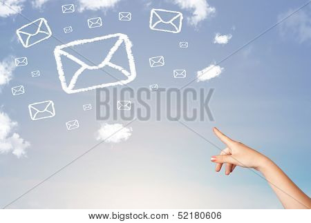 Hand pointing at mail symbol and icon clouds on blue sky