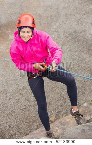 Happy girl abseiling down rock face looking up at camera