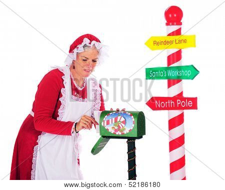 Mrs. Claus getting mail from Santa's mailbox next to a candy striped pole with directions to Santa.  On a white background.