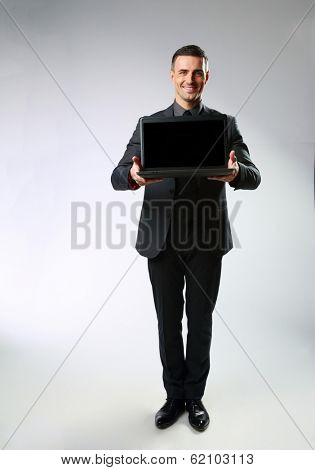 Full-length portrait of a businessman standing with laptop on gray background