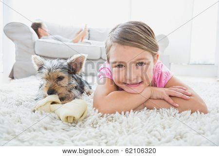 Little girl lying on rug with yorkshire terrier smiling at camera at home in the living room