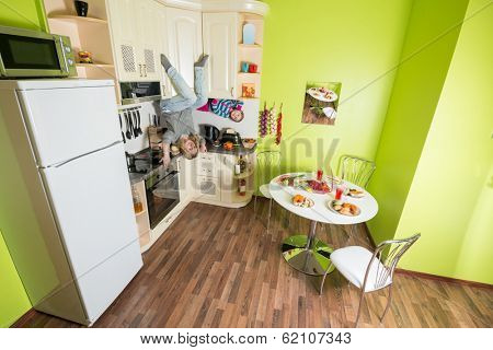 Mother and daughter sitting at shelves upside down in the kitchen