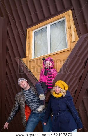 Family of three against the roof of real inverted house