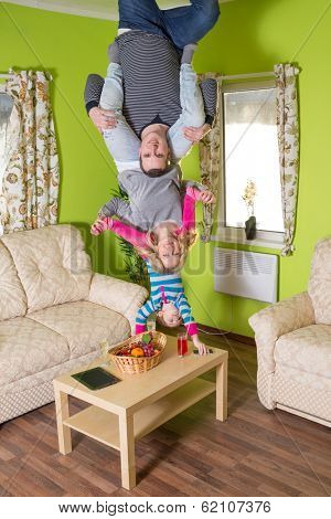 Family of three upside down on the ceiling at inverted house