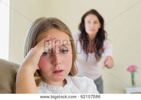 Disappointment girl with mother scolding her in background at home