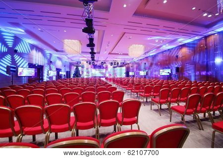 Conference  hall with red chairs and colored illumination