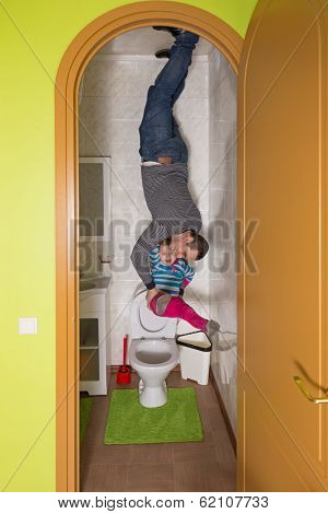 Father with daughter upside down on the ceiling in toilet at inverted house