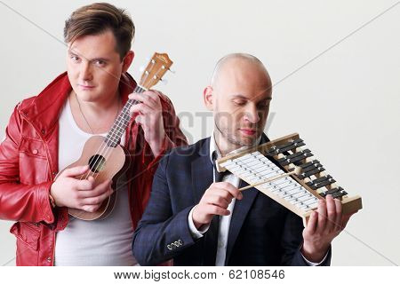 Two young men with musical instruments, focus on the right man.