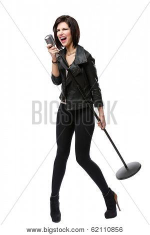 Full-length portrait of rock singer wearing leather jacket and handing static microphone, isolated on white. Concept of rock music and rave