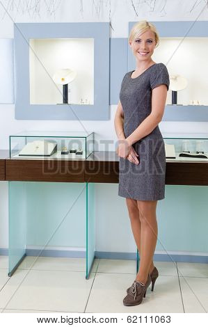 Shop assistant stands near the window case at jeweler's shop. Concept of wealth and luxurious life