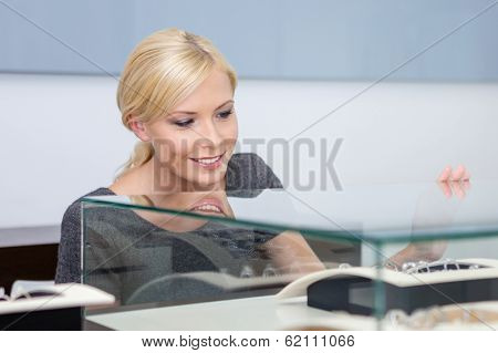 Close up of girl looking at jewelry in glass case at jeweler's shop. Concept of wealth and luxurious life