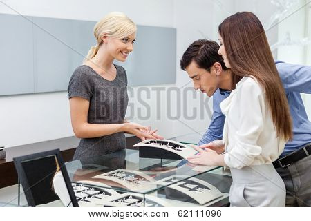 Salesperson helps couple to select jewelry at jeweler's shop. Concept of wealth and luxurious life