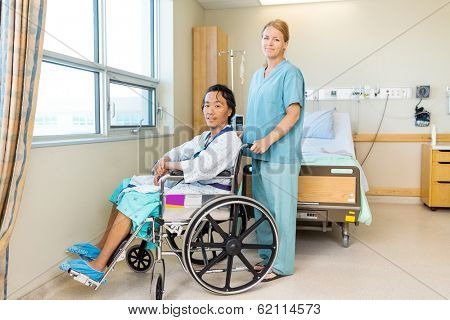 Full length portrait of male patient sitting on wheel chair while nurse standing behind at window in hospital