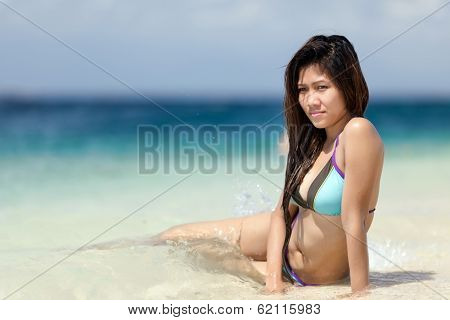 Beautiful young Filipina woman at the seaside sitting in the shallow tranquil blue ocean in a bikini enjoying the hot tropical summer sun, with copyspce