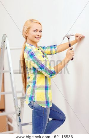 reapir, building and home renovation concept - smiling woman hammering nail in wall