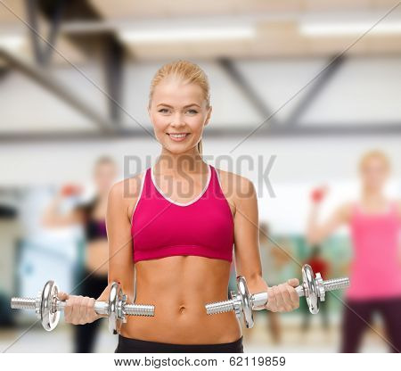 fitness, healthcare and dieting concpt - young sporty woman with heavy steel dumbbells