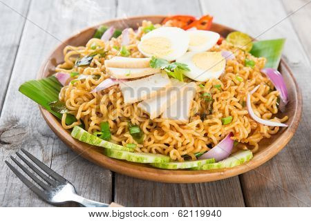 Dry Instant Noodle, Malaysian style maggi goreng mamak or spicy dry curry instant noodles. Asian cuisine, ready to serve on wooden dining table setting. Fresh hot with steamed smoke.