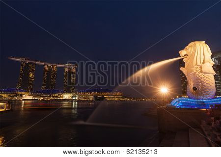 SINGAPORE - JANUARY 1, 2014: Night view of Singapore Merlion at Marina Bay and Marina Bay Sand complex. Merlion is a well-known tourist icon, mascot and national personification of Singapore