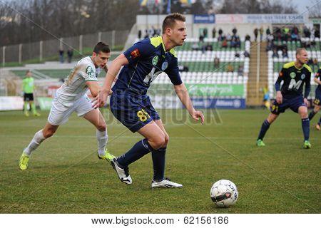 KAPOSVAR, HUNGARY - MARCH 16: Adrian Szekeres (blue 89) in action at a Hungarian Championship soccer game - Kaposvar (white) vs Puskas Akademia (blue) on March 16, 2014 in Kaposvar, Hungary.