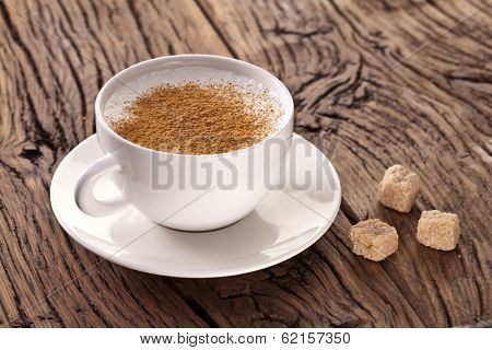 Cup of cappuccino with ground cinnamon and sugar cubes on the plate.